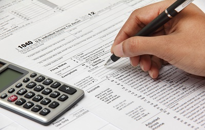 hand filling out tax document with calculator
