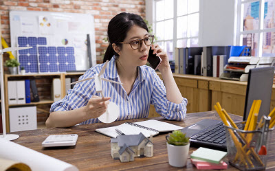 small business owner talking on phone while working in office with laptop